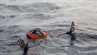 NOVEMBRE. Un migrant sur le point d'être secouru par l'ONG allemande Sea-Watch, le 6 novembre 2017 au large de la Libye. (ALESSIO PADUANO / AFP)