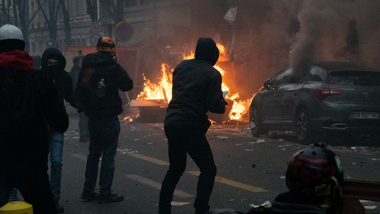 """Un individu devant un feu lors de la manifestation parisienne contre la proposition de loi sur la """"sécurité globale"""", théâtre d'affrontements entre la police et des """"blacks blocs"""", le 5 décembre 2020. (ESTELLE RUIZ / HANS LUCAS / AFP)"""