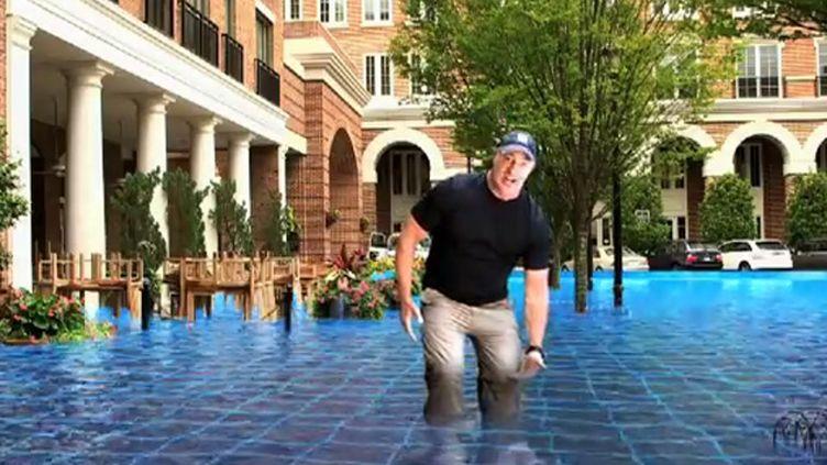 (Le journaliste américain Jim Cantorry les pieds dans l'eau en 2050 © Capture d'écran Youtube)