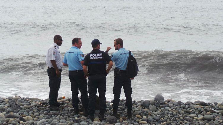 Des gendarmes et des policiers sur la plage où a été découvert un débris d'avion, mercredi 29 juillet 2015, à Saint-André, sur l'île de La Réunion. (REUTERS)