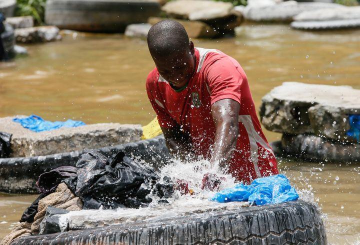 Un fanico en plein effort frappe le linge sur un pneu placé au milieu de la rivière. (MAHMUT SERDAR ALAKUS / ANADOLU AGENCY)