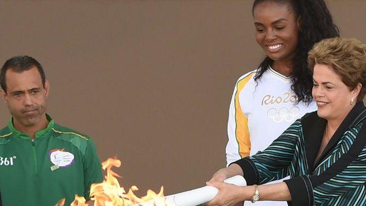La présidente Dilma Rousseff remet la flamme olympique à la joueuse de volley-ball brésilienne Fabiana Claudino, le 3 mai 2016, au Palais du Planalto à Brasilia. (EVARISTO SA / AFP)