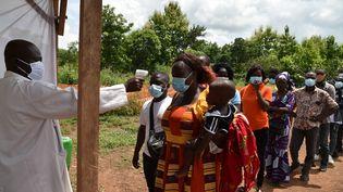Des agents du ministère de la Santé de la Côte d'Ivoire mesurent la température corporelle des passagers à un poste de contrôle à l'entrée de Bouaké, le 25 juin 2020. (ISSOUF SANOGO / AFP)