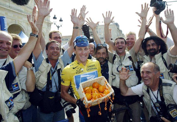 Lance Armstrong pose avec les photographes du Tour qui lui ont attribué le prix Orange du coureur le plus sympathique de la Grande Boucle, à Bordeaux, le 25 juillet 2003. (BERND THISSEN / DPA)