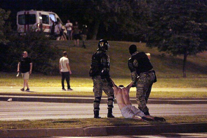 Deux militaires anti-émeutes tirent par les bras un manifestant, le 9 août 2020, à Minsk. (SIARHEI LESKIEC / AFP)