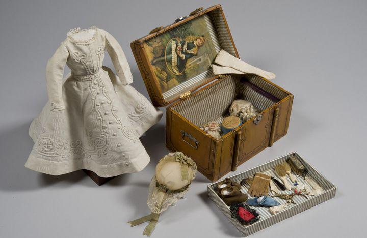 Robe et valise de poupée avec accessoires. Paris, 1850-1900. Inv. F. 1340 & F.7994. L. 25 cm (robe) , H. 15 x L. 23,5 x l. 15 cm (valise)  (Musées royaux d'art et d'histoire )