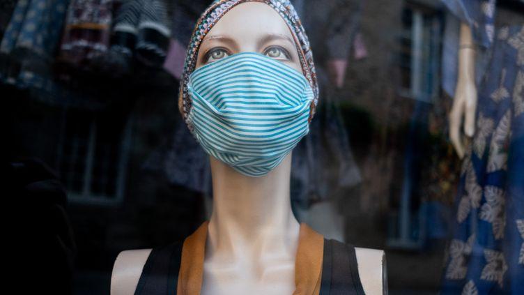 Un masque réutilisable dans une vitrine à Dinan (Côtes-d'Armor), le 26 mai 2020. (MARTIN BERTRAND /  AFP)
