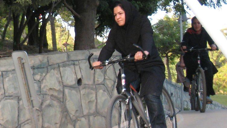 """Une Iranienne fait du vélo dans le parc de Téhéran """"Le paradis des mères"""" qui est une aire de la capitale réservée aux femmes, le 13 juin 2008. (BEHROUZ MEHRI / AFP)"""