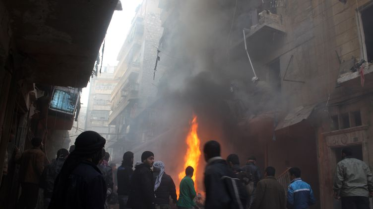 Des habitants d'Alep constatent les dégâts d'un bombardement aérien sur cette ville du nord de la Syrie, le 15 décembre 2013. (MOHAMMED AL-KHATIEB / AFP)
