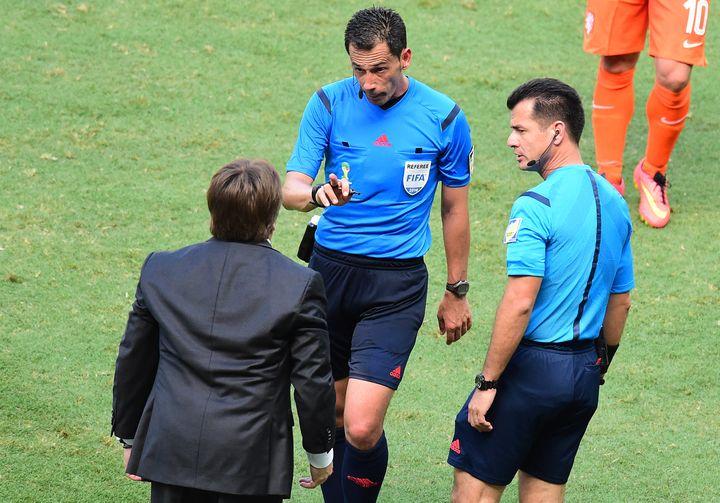 L'arbitre portugais Pedro Proença recadre le sélectionneur mexicain Miguel Herrera, le 29 juin 2014 lors du match Pays-Bas-Mexique, au stade Castelao de Fortaleza (Brésil). (JAVIER SORIANO / AFP)