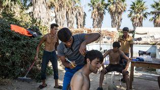 Un migrant se fait faire une coupe de cheveux improvisée à l'hôtel désaffectéCaptain Elias, devenu un refuge de fortune, le 19 août 2015. (KONSTANTINOS TSAKALIDIS / SOOC)