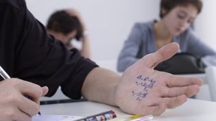 Un jeune homme regarde son antisèche lors d'une épreuve de mathématiques. (FUSE / GETTY IMAGES)