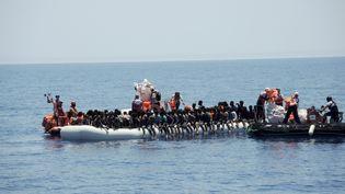 Des membres des ONG Médecins sans frontières et SOS Méditerranée viennent en aide à des migrants dans la mer Méditerranée, le 27 juin 2017. (LENA KLIMKEIT / AFP)
