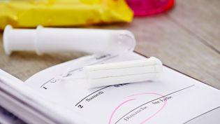 Un tampon déballé repose sur un agenda qui rappelle la régularité du cycle menstruel, illustration du 2 juillet 2015. (ALICE S. / AFP)