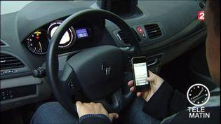 Un homme regardant son téléphone au volant de sa voiture (FRANCE 2)
