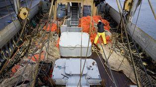 """Un pêcheur sur le bateau de pêche néerlandais """"TX-38 Branding IV"""" prépare les filets de pêche à impulsion électrique lors du départ du port de Den Helder (Pays-Bas), le 18 janvier 2018. (NIELS WENSTEDT / ANP / AFP)"""