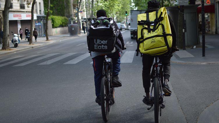 Deux livreurs à vélo dans les rues de Paris, pendant l'épidémie de coronavirus, le 3 mai 2020. (VICTOR VASSEUR / RADIOFRANCE)