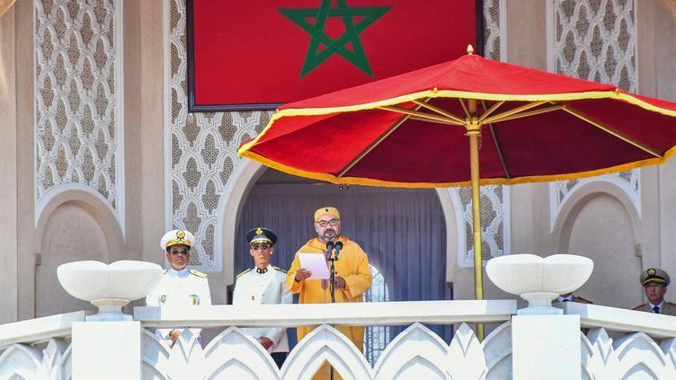 Le roi du Maroc Mohammed VI (C) prononçant un discours marquant le 20e anniversaire de son accession au trône, avec son frère le prince Moulay Rachid (R) et son fils le prince Moulay Hassan. (L) assis à ses côtés, dans la ville de Tétouan le 29 juillet 2019. (DRISS BEN MALEK / MOROCCAN ROYAL PALACE)