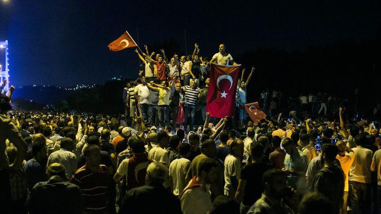 Des manifestants sur un pont à Istanbul (Turquie) pour protester contre le coup d'Etat de certains militaires, le 16 juillet 2016. (GURCAN OZTURK / AFP)