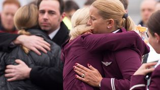 Des employés de la compagnie aérienne allemande Germanwings s'enlacent après une minute de silence à la mémoire des victimes du crash aérien de l'A320 dans les Alpes françaises, Cologne (Allemagne), le 25 mars 2015. (MARIUS BECKER / DPA / AFP)