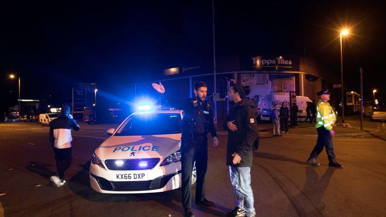 Un policier britannique oriente un passant à proximité de la Manchester Arena, une salle de concert où une possible explosion a fait plusieurs morts, le 22 mai 2017 à Manchester. (REUTERS)