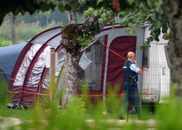 """Un gendarme surveille la caravane de la famille Al-Hilli, installée dans lecamping """"Le Solitaire du lac"""", à Saint-Jorioz (Haute-Savoie),jeudi 6 septembre. (PHILIPPE DESMAZES / AFP)"""
