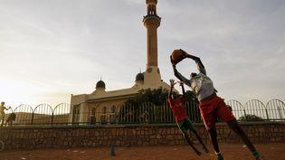 Des enfants jouent au foot devant une mosquée, à Niamey (Niger), le 14 septembre 2011. (SIA KAMBOU / AFP)