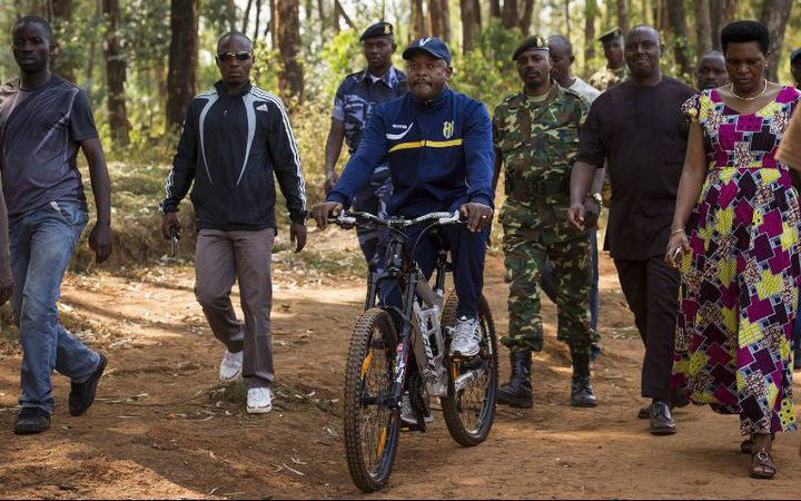 Le président Pierre Nkurunziza arrive, à vélo, à son bureau de vote dans son village natal de Buye, le 21 juillet 2015. (Photo AFP/Philip Moore)
