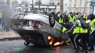 """Une voiture est incendiée à côté des Champs-Elysées par des """"gilets jaunes"""". (ALAIN JOCARD / AFP)"""