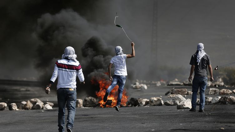 Des manifestants palestiniens jettent des pierres vers les forces de sécurité israéliennes et de pneus enflammés dans la ville cisjordanienne d'Al-Bireh, périphérie de Ramallah, le 20 Octobre 2015 (THOMAS COEX / AFP)