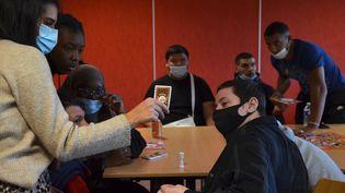 """Des bénéficiaires de la """"garantie jeunes""""déchiffrent un rébus lors d'un atelier nutrition animé par une conseillère de la mission locale de Romilly-sur-Seine (Aube), le 14 octobre 2021. (YANN THOMPSON / FRANCEINFO)"""