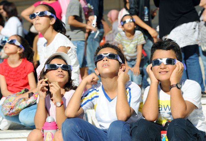 Des enfants regardent une éclipse solaire depuis Tunis au moyen de lunettes spéciales, le 3 novembre 2013. (FETHI BELAID / AFP)
