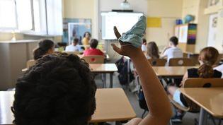 Un élève participant en classe, un masque sanitaire à la main, le 10 aout 2020, dans une école berlinoise. (TOBIAS SCHWARZ / AFP)
