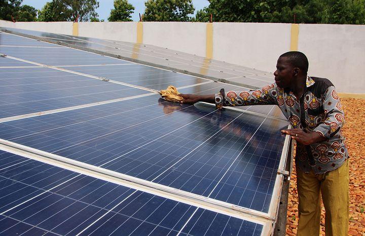 Un technicien nettoie les panneaux solaires mis en place par Bboxx et EDFdans le village de Sikpe Afidegnon au Togo, le 16 mai 2019.     (REUTERS / NOEL KOKOU)