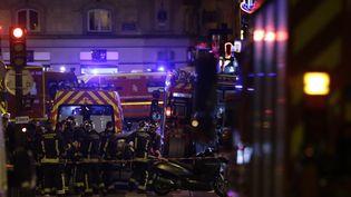 Des pompiers prennent en charge des blessés, lors des attentats du 13 novembre 2015, à Paris. (KENZO TRIBOUILLARD / AFP)