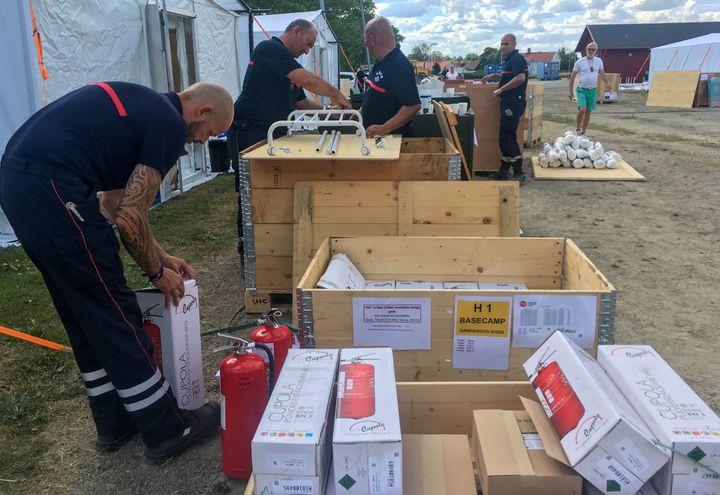 Des pompiers français installent leurs affaires dans le camp de base de Färila, le 24 juillet 2018. (ELISE LAMBERT / FRANCEINFO)