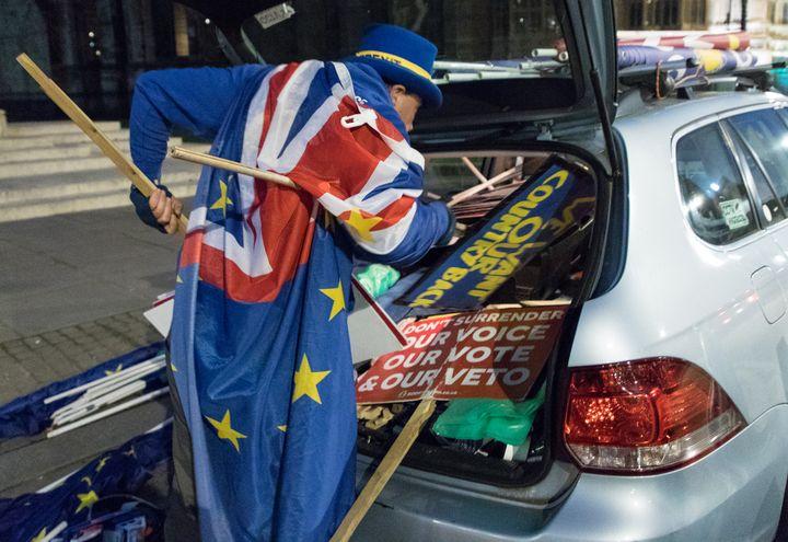 Steve Bray tente de ranger ses pancartes dans sa voiture, le 25 février 2019, à Londres (Royaume-Uni). (MARIE-VIOLETTE BERNARD / FRANCEINFO)
