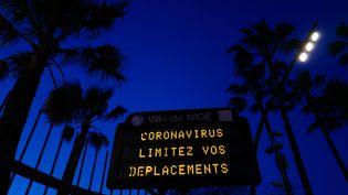 Un panneau d'affichage municipal à Nice, le 16 mars 2020, demandant aux habitants de limiter leurs déplacements à cause de l'épidémie de coronavirus. (VALERY HACHE / AFP)