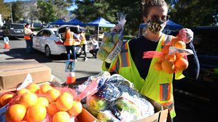 En Californie, aux États-Unis, des bénévoles participent à une distribution de denrées alimentaires pour les plus démunis. (ROBYN BECK / AFP)