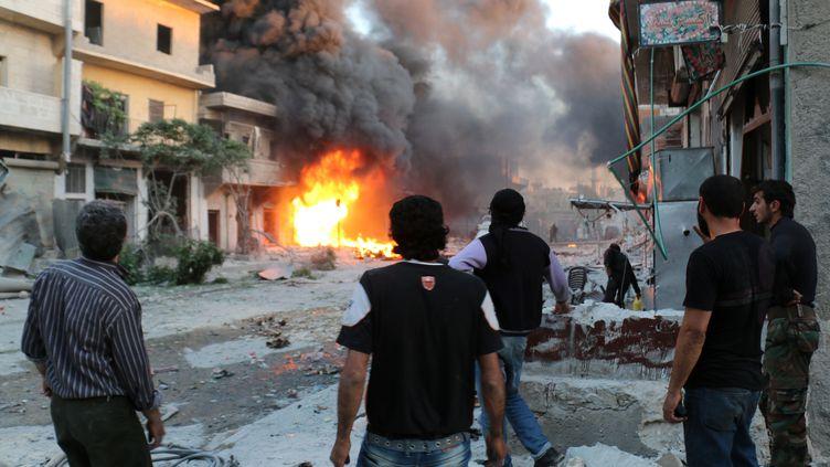 Des combattants rebelles et des civils assistent à l'incendie d'un immeuble dans la ville d'Alep (Syrie), le 20 avril 2014. (ZEIN AL-RIFAI / ALEPPO MEDIA CENTRE)