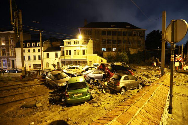 Des voitures endommagées par la pluie et transportées par les inondations sont empilées dans une rue de Dinant, en Belgique, le 24 juillet 2021. (DURSUN AYDEMIR / ANADOLU AGENCY / AFP)