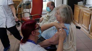 """Une résidente de la maison de retraite """"Les Oyats"""", à Gravelines (Nord), se fait vacciner contre le Covid-19, le 15 janvier 2021.  (SYLVAIN LEFEVRE / HANS LUCAS / AFP)"""