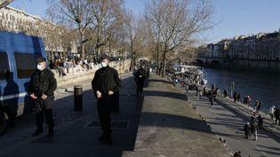 Des policiers le long des quais de Seine, à Paris, le 26 février 2021. (THOMAS COEX / AFP)