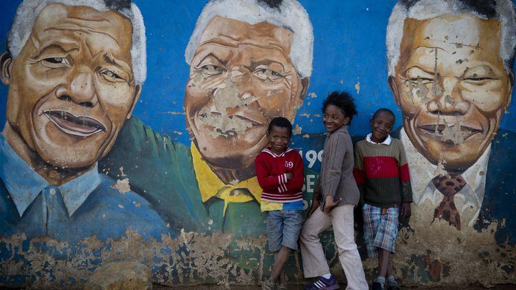 Des enfants posent devant des portraits de Nelson Mandela, àSoweto (Afrique du Sud), le 26 juin 2013. (ODD ANDERSEN / AFP)