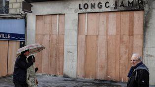 Des passants marchent devant la boutique Longchamp, dont les vitrines ont été remplacées par des panneaux de bois. (GEOFFROY VAN DER HASSELT / AFP)
