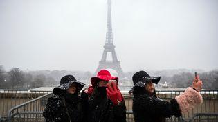 Des touristes se prennent en photo devant la tour Eiffel, à Paris, le 5 février 2018. (LIONEL BONAVENTURE / AFP)