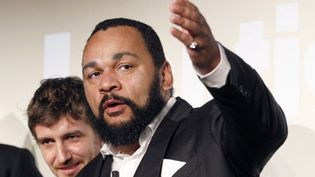 "FRANCE, Paris : French controversial humorist Dieudonné Mbala Mbala (R) next to members of his film unit prior to the premiere screening of his movie ""Antisémite"" (Anti-Jewish) on January 15, 2012 on the stage of the ""Main d'Or"" theatre in Paris. AFP PHOTO PATRICK KOVARIK  (AFP)"