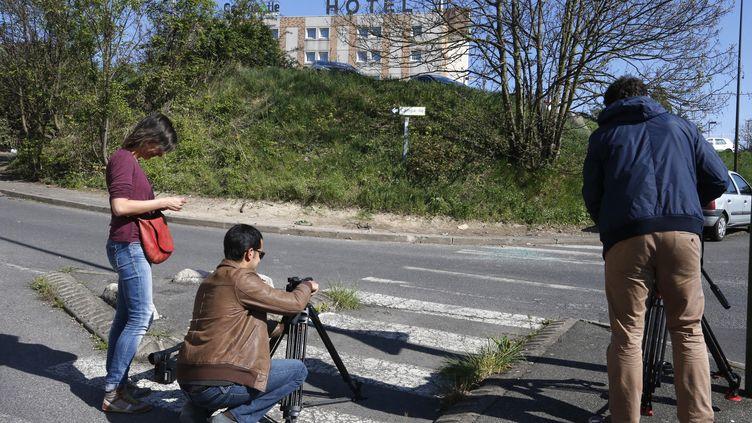 Des journalistes filment la scène, le 19 avril 2015,où a été découvert le véhicule brûlé et le corps d'Aurélie Châtelain, à Villejuif (Val-de-Marne). (FRANCOIS GUILLOT / AFP)
