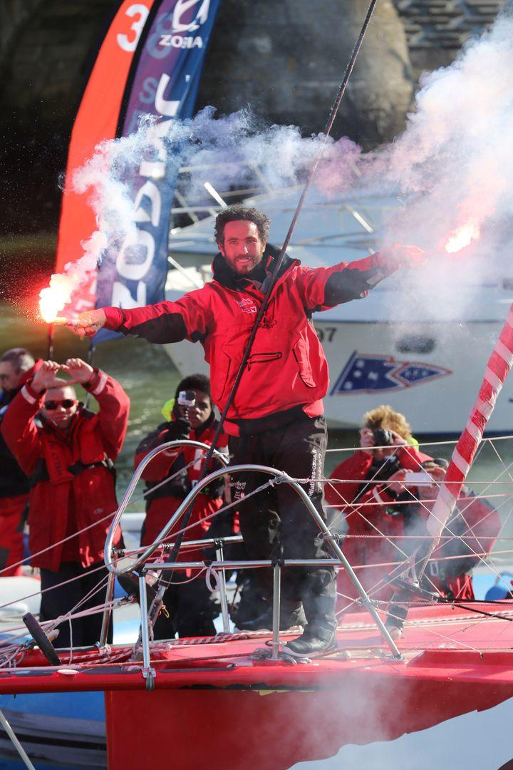 Le skipper Tanguy de Lamotte fête son arrivée aux Sables d'Olonne,le 17 février 2013. (JEAN-MARIE LIOT / DPPI / AFP)
