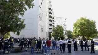 Policiers et habitants du quartier dans la Cité des Flamants, dans le 14e arrondissement de Marseille (Bouches-du-Rhône) le 17 juillet 2021, après l'incendie qui a fait trois morts et plusieurs blessés (FRANCK PENNANT / MAXPPP)